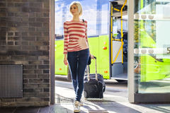 Female traveler going off the bus at terminal Royalty Free Stock Image