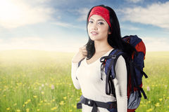 Female traveler with hiking bag on meadow Stock Photos