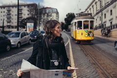 Female traveler holding and reading tourist map. Waiting the tram,using public transportation in foreign country.Tourist in Lisbon,Portugal awaiting iconic royalty free stock photography