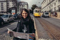 Female traveler holding and reading tourist map. Waiting the tram,using public transportation in foreign country.Tourist in Lisbon,Portugal awaiting iconic stock photo