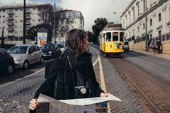 Female traveler holding and reading tourist map. Waiting the tram,using public transportation in foreign country.Tourist in Lisbon,Portugal awaiting iconic royalty free stock photo