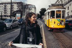Female traveler holding and reading tourist map. Waiting the tram,using public transportation in foreign country.Tourist in Lisbon,Portugal awaiting iconic stock photography