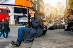 Female traveler in London sits at the steps of Piccadilly Circus square stock image