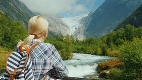 A female traveler looks at the beautiful mountains and glacier on top. Briksdal glacier in Norway royalty free stock images