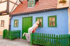 Female traveler looks on the window in Golden Lane, Prague, Czech Republic. Female traveler looks on the window of colorful little house in Golden Lane in the royalty free stock photo
