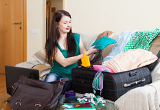 Female traveler packing suitcase for holiday. At home Royalty Free Stock Image
