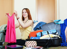 Female traveler packing suitcase at home Royalty Free Stock Images