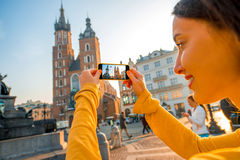 Female traveler photographing with mobile phone in Krakow Royalty Free Stock Photography