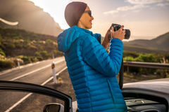 Female traveler photographing sunrise near the car Stock Images