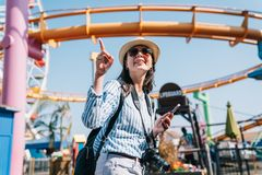 A female traveler pointing to roller coaster stock images