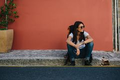 Female traveler resting on the sidewalk royalty free stock photography