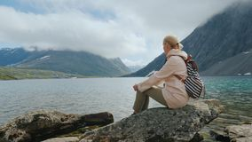 A female traveler sits on a big rock admiring the majestic mountain lakes in Norway stock image