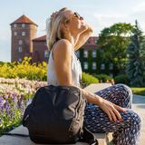 Female traveler sitting and enjoys the view of Wawel Castle. Royalty Free Stock Image