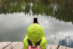 A female traveler is sitting on a wooden pier near a beautiful lake in a pine forest and taking photos on mobile phone. Stock Photography