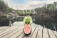 A female traveler is sitting on a wooden pier near a beautiful lake in a pine forest and taking photos on mobile phone. Royalty Free Stock Photography