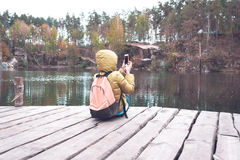 A female traveler is sitting on a wooden pier near a beautiful lake in a pine forest and taking photos on mobile phone. Royalty Free Stock Image