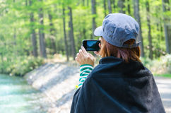 Female traveler with smart phone taking a photo at kamikochi nagano japan Stock Photo