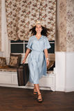Female traveler standing in the room with luggage. Royalty Free Stock Photography