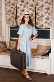 Female traveler standing in the room with luggage. Royalty Free Stock Photos