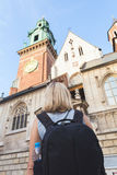 Female traveler stands and admires the view of Wawel Cathedral, Cracow, Poland Royalty Free Stock Image