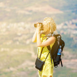 Female traveler stands on hill and takes pictures Royalty Free Stock Photo