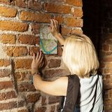 Female traveler stands and studying the city map. Krakow, Poland. Female traveler stands and studying the city map on the background of old age brick wall within royalty free stock photography