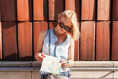 Female traveler stands and studying the city map. Krakow, Poland. Female traveler stands and studying the city map on the background of old age brick wall stock photos