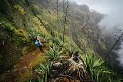 Female traveler staying on the cove volcano edge above the foggy green valley overgrown with agaves Santo Antao island. In Cabo Verde Royalty Free Stock Photography