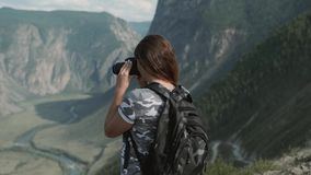 Female traveler takes beautiful pictures with the camera while standing at the peak of the mountain. Female traveler with a backpack takes beautiful pictures stock video