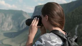 Female traveler takes beautiful pictures using the camera while standing at the peak of the mountain. Close-up. A female traveler with a backpack takes beautiful stock video footage