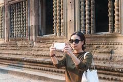 Female traveler taking photo with her smartphone in angkor wat cambodia stock image