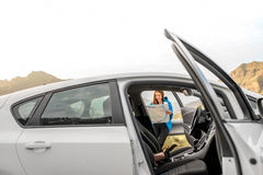 Female traveler with toursit map near the car Stock Images