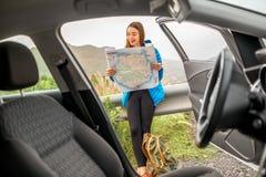 Female traveler with toursit map near the car Stock Photo