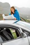 Female traveler with toursit map near the car Stock Photos