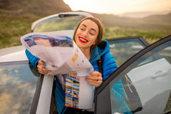 Female traveler with toursit map near the car Royalty Free Stock Photography