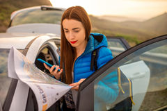 Female traveler with toursit map near the car Royalty Free Stock Image