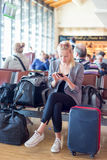 Female traveler using cell phone while waiting on airport. Royalty Free Stock Photography