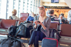 Female traveler using cell phone while waiting on airport. Stock Image