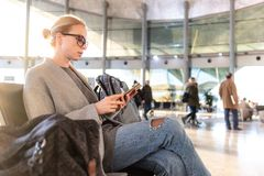Female traveler using her cell phone while waiting to board a plane at departure gates at airport terminal. stock photos