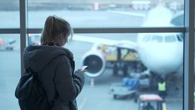 Female traveler waiting for departure and using her cellphone. a young girl writes a message. Waiting for the flight.  stock video footage
