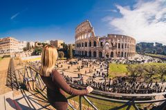Female traveler watching over the Colosseum in Rome, Italy. The most famous symbol of Rome, visited yearly by millions of tourists from around the world. The Royalty Free Stock Photography
