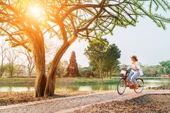 Female Traveler Weared Light Summer Clothes And Hat Have Early Morning Bicycle Walk In Ayutthaya Historical Park, Thailand Royalty Free Stock Image