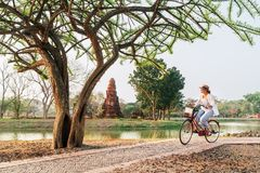 Female traveler weared light summer clothes and hat have early morning bicycle walk in Ayutthaya historical park, Thailand stock image