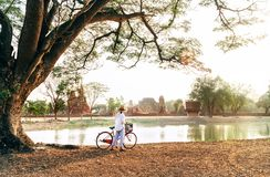 Female traveler weared light summer clothes and hat have early morning walk with bicycle near pond in Ayutthaya historical park, royalty free stock photo