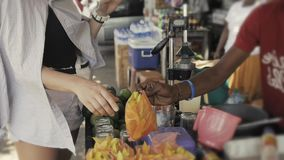 Female traveler woman buying fresh tropical mango fruit with pepper on traditional street food market in asia. Female traveler woman buying fresh tropical fruit stock footage