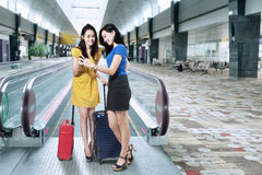 Female travelers with cellphone in airport Stock Photos