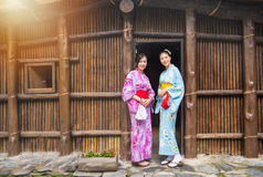 Female travelers wearing traditional clothing. Elegant female travelers wearing traditional clothing dress kimono standing in front of old wooden house door Stock Photo