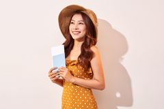 Female traveling abroad to travel weekends getaway. Expressive tourist woman in summer casual clothes, hat holding passport, tickets isolated on beige royalty free stock photos