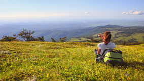 Female traveller with backpack making photo of mountain lanscape. Young female traveller with backpack and long brown hair sitting at green grass glade and Stock Images