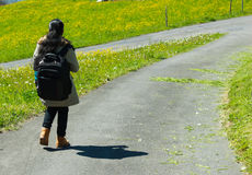 Female traveller with backpack walking along trail of green road. Female traveller with backpack walking along trail of road with green grass on both sides. The Stock Photo